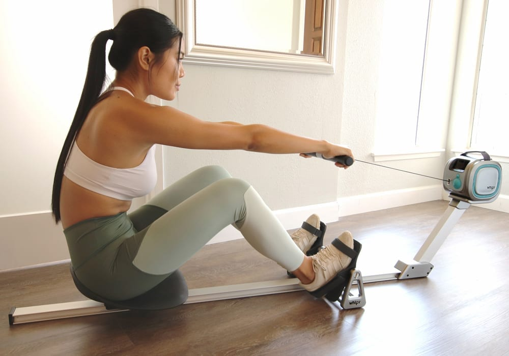 Person working out using whipr rowing machine attachment